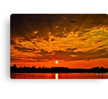 Flight travels through the skies when sun goes down Canvas Print