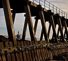 Lighthouse through the wooden pier by Violaman