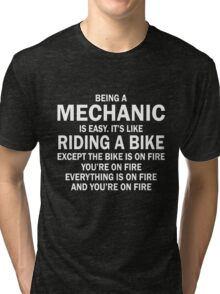 BEING A MECHANIC IS EASY.IT'S LIKE RIDING A BIKE EXCEPT THE BIKE IS ON FIRE YOU'RE ON FIRE EVERYTHING IS ON FIRE AND YOU'RE ON FIRE Tri-blend T-Shirt