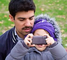 Father And Daughter Taking Photographs  by Kuzeytac