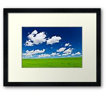 Green rolling hills under blue sky Framed Print