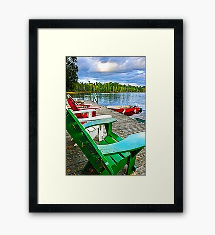 Deck chairs on dock at lake Framed Print