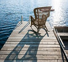Rocking chair on small lake dock by Elena Elisseeva