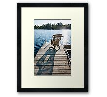 Rocking chair on small lake dock Framed Print