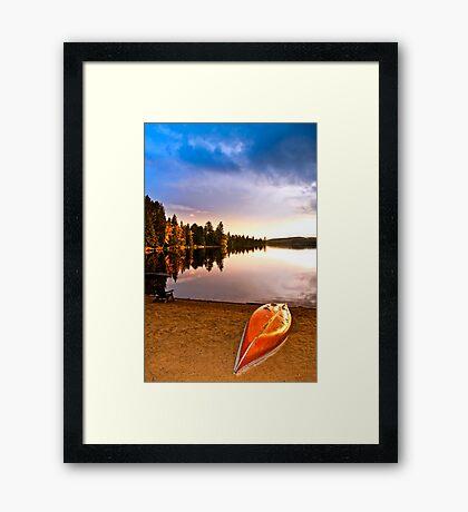 Lake sunset with canoe on beach Framed Print