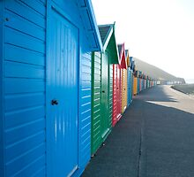 Row of brightly coloured beach huts by photoeverywhere