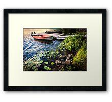 Rowboat at lake shore at dusk Framed Print