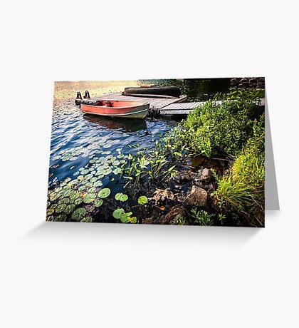Rowboat at lake shore at dusk Greeting Card