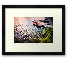 Rowboat at lake shore at sunrise Framed Print