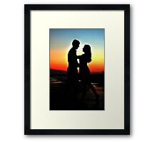 Silhouette of a loving couple against a decline Framed Print