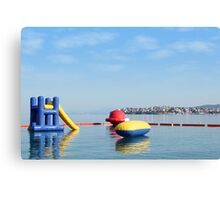 beach toys and equipment floating on sea Canvas Print