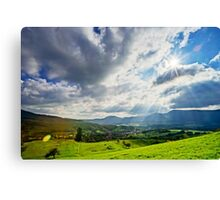 Sun shining through the clouds over beautiful green valley Canvas Print