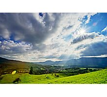 Sun shining through the clouds over beautiful green valley Photographic Print