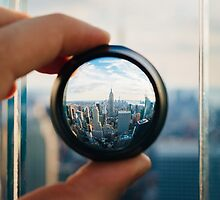 Man holding a lens over Manhattan by Giorgio Fochesato