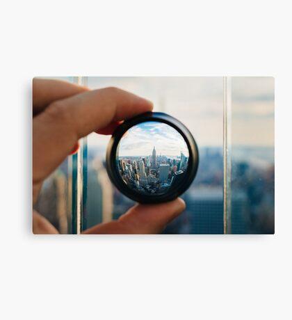 Man holding a lens over Manhattan Canvas Print