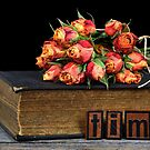 orange rose bouquet on vintage book by Maria Dryfhout
