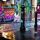 Bollards in a Rainy Graffiti Lane by jamjarphotos