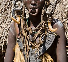 Woman of the Mursi with elongated lower lip to hold a clay disk as body ornament by PhotoStock-Isra