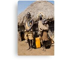 Mursi couple. The woman has an elongated lower lip to hold a clay disk as body ornament Canvas Print