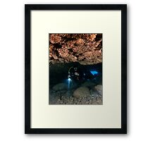 Divers explore natural caves and rocks in the Mediterranean sea off the coast of Larnaca, Cyprus,  Framed Print