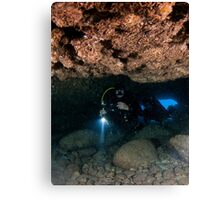 Divers explore natural caves and rocks in the Mediterranean sea off the coast of Larnaca, Cyprus,  Canvas Print