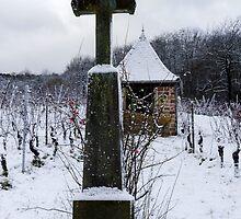 Religious cross in winter snowy vineyard, Alsace, France by Alexander Sorokopud
