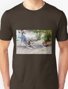 A mature dog and a puppy play in the yard  Unisex T-Shirt