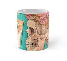 illustration with skull holding a human face mask Mug