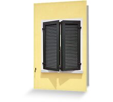 Partly opened green window shutters on bright yellow wall with great shadows Greeting Card