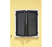 Partly opened green window shutters on bright yellow wall with great shadows Photographic Print