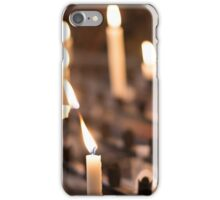 Woman lighting prayer candle aka offering, sacrificial or memorial candles lit in a church iPhone Case/Skin