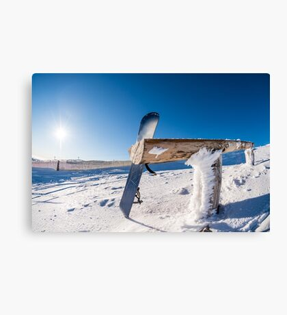 Snowboard leaning on a wood rail Canvas Print