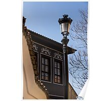 Perfectly Aligned - Intricate Ironwork Streetlight and Classic Revival House Poster