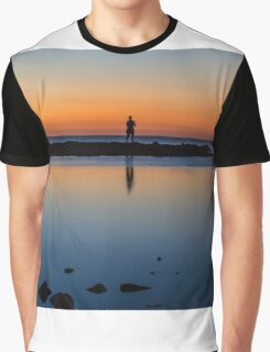 Silhouette of a man on some rocks at the beach Graphic T-Shirt
