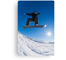 Snowboarder jumping against blue sky Canvas Print