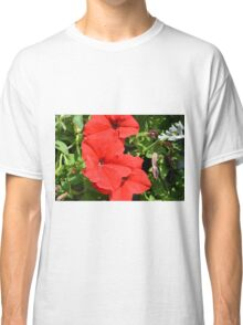Red flowers on green leaves background. Classic T-Shirt