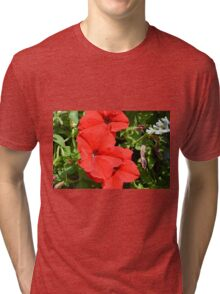 Red flowers on green leaves background. Tri-blend T-Shirt
