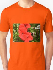 Red flowers on green leaves background. Unisex T-Shirt