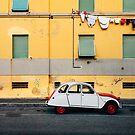 Vintage Car Parked in Front of Yellow Apartment Building in Italy by visualspectrum