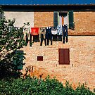 Laundry Drying on Washing Line Against Old Brick Building in Tuscany Italy by visualspectrum