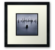 Calm sea and wooden sticks Framed Print