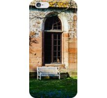 Lonely bench under the wall of old church. Spring lawn with blue florets. iPhone Case/Skin