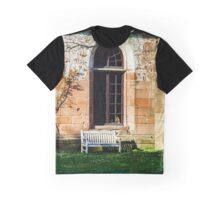 Lonely bench under the wall of old church. Spring lawn with blue florets. Graphic T-Shirt