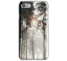 Sunlight burning through mist in a dense woodland. Thetford Forest, Norfolk, UK. iPhone Case/Skin