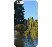 Beautiful spring garden with willow tree by a pond and water fountain iPhone Case/Skin