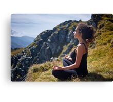 Woman practicing yoga on mountain Canvas Print