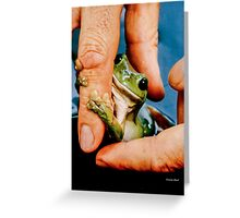Green bush frog hanging onto finger Greeting Card