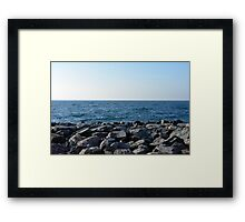 The sea and blue sky, and rocks at the shore. Framed Print