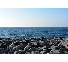 The sea and blue sky, and rocks at the shore. Photographic Print
