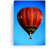 Red hot air balloon in flght on blue sky. Canvas Print